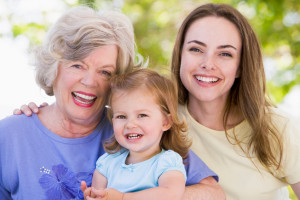 Grandmother with adult daughter and grandchild relaxing in park